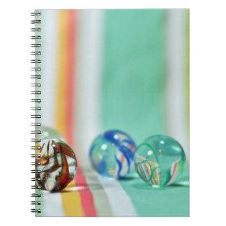 Marmorar på en randig bakgrund anteckningsbok med spiral