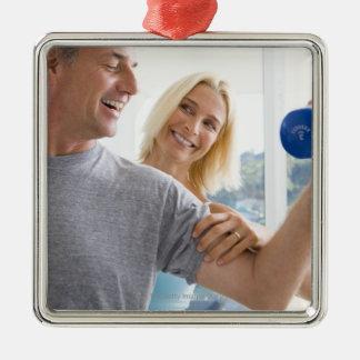 Mogna kvinnan som ler på, mognar att lyfta för man julgransprydnad metall