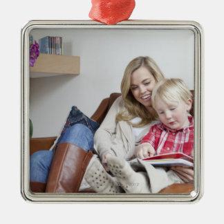 Mor- och sonsitta på soffan tillsammans julgransprydnad metall