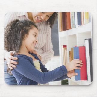 Morportiondottern väljer boken på hylla musmatta
