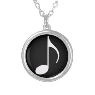 musikalen noterar, svärtar silverpläterat halsband
