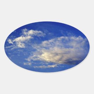 Mycket strukturerat moln i en härlig blå himmel ovalt klistermärke