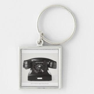 Närbild av en roterande telefon fyrkantig silverfärgad nyckelring