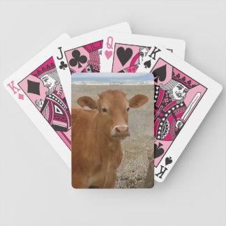 Nätt rött konötkreatur vänder mot westernt spelkort