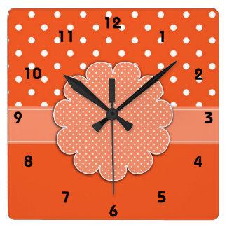 Orange- och vitpolkaen pricker väggen tar tid på fyrkantig klocka