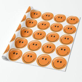 Orange smiley face som slår in papper presentpapper