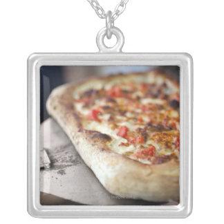 Pizza med tomater, vitlök och kött ersätter silverpläterat halsband