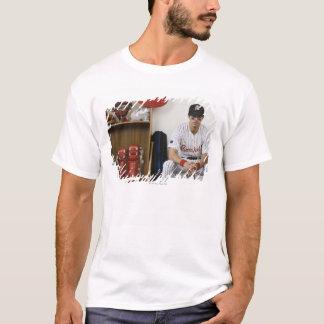 Porträtt av basebollspelaresitta i skåp tröjor