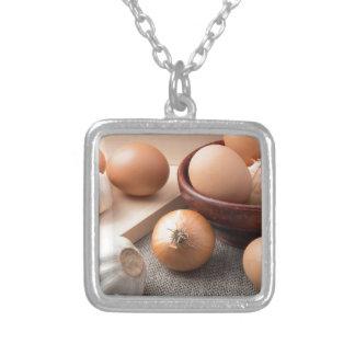 Rå ägg, lökar och vitlök på en bakgrund silverpläterat halsband