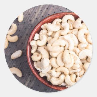 Rå cashewnöt i en brun bunke på tyg runt klistermärke
