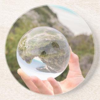 Räcka den hållande kristallkulan nära havet och underlägg