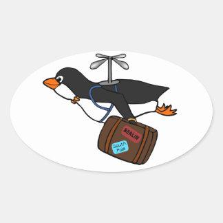 Resande flyghelikopterpingvin med resväska ovalt klistermärke