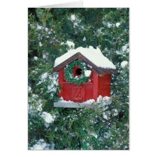 Röd ladugårdbirdhouse som dekoreras med en kran hälsningskort