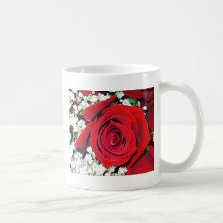 Röd ros och brudslöja på en klassikerkopp kaffe koppar