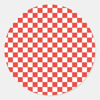 Röd schackbräde runt klistermärke