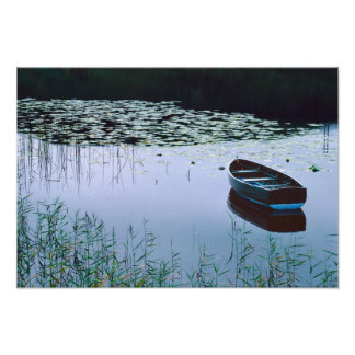 Roddbåt på den små sjön som omges av vatten fototryck