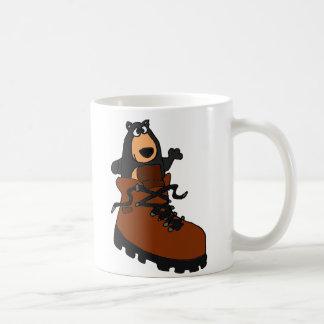 Rolig svart björn i brun fotvandra känga kaffemugg