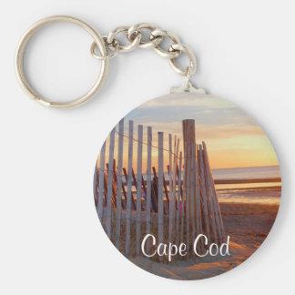 Romantisk uddtorsk samlas soluppgång över stranden rund nyckelring