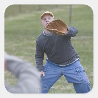 Rörelsehindrad man som leker baseball med hans son fyrkantigt klistermärke