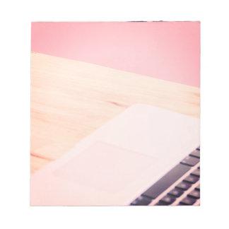 Rosa dator på memoen för skrivbordfotoinspiration anteckningsblock