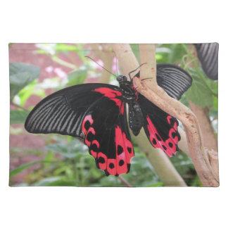 Rosa och svart fjäril på grenbordstablett bordstablett