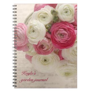 rosa- och vitranunculusen skrivar på anteckningsbok med spiral