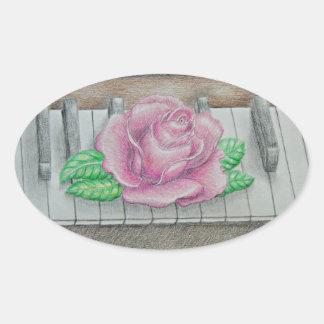 Rosa ros på piano ovalt klistermärke