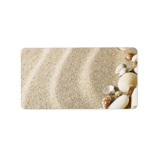 Sand med snäckor och stenar. Strandsammansättning Adressetikett