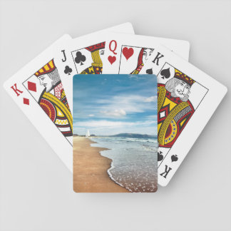 Sandig strand som leker kort spelkort