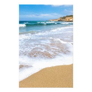 Sandigt strandhav som är vinkart, och berg på brevpapper
