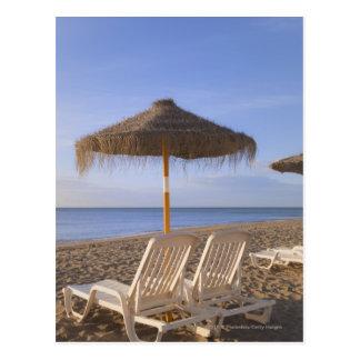 Sandstrandstolar med paraplyet vykort