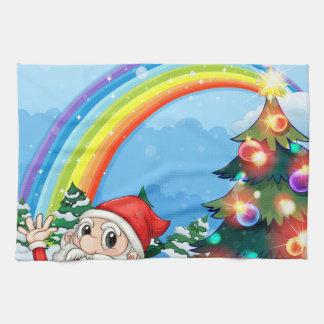 Santa sitta bredvid gåvan nära regnbågen kökshandduk