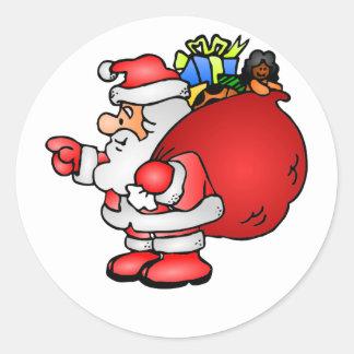 Santas hänger lös av presenter runt klistermärke