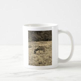 Sepia tonar åsnan i ett fält vit mugg