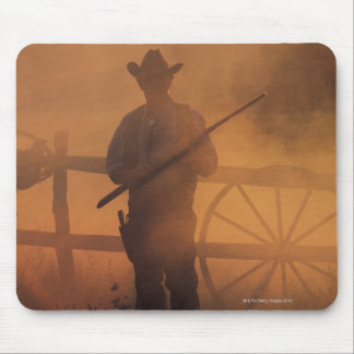 Silhouetten av cowboyen med geväret räcker in musmatta