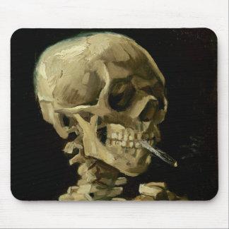 Skalle av ett skelett med den brinna cigaretten mus matta