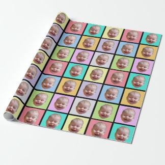 Skratta babyansikte på mångfärgade kvarter presentpapper