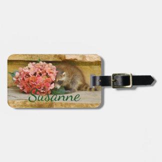 Skygga babyraccoonen bak blom- bukett bagagebricka