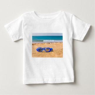 Slösa simninggoggles som ljuger på stranden med tshirts