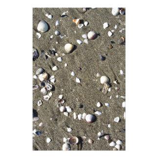 Snäckor på sanden. Sommarstrandbakgrund Brevpapper