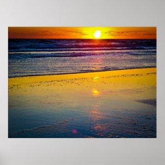 Soluppgång över hav & reflekterad på strand poster