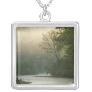 Soluppgång till och med dimma som beskådas från silverpläterat halsband