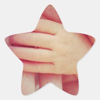 Spädbarn räcker stjärnformat klistermärke