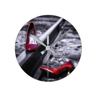 Sparka av ditt skor rött skor på järnväg spårar rund klocka