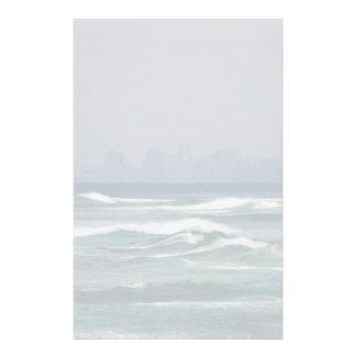 Stadshorisont bak vågar av hav brevpapper