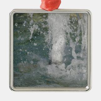 Stänk av fontänvatten i en solig dag julgransprydnad metall