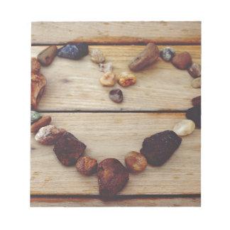 Stenkärlekhjärta på brunt trä anteckningsblock