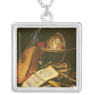 Stilleben med musikal instrumenterar silverpläterat halsband