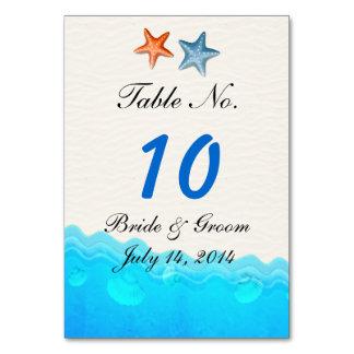 Strand med kortet för sjöstjärnabröllopbord bordsnummer