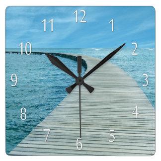 Strandlivhav beskådar väggen tar tid på fyrkantig klocka